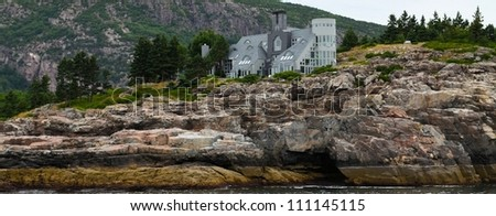 A home on the ocean in Maine. Shown along the rocky coasr - stock photo