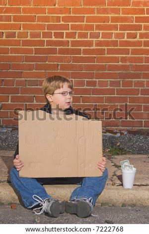 A homeless boy with a blank cardboard sign. - stock photo