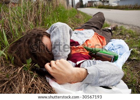 A homeless drunk person laying by the edge of the road - stock photo