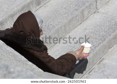 A homeless female begger is begging at the subway underpass stairs in the center of Sofia. - stock photo