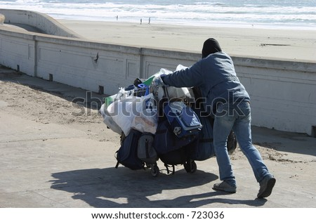 A homeless guy pushes a shopping cart along the sea wall.