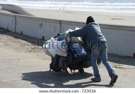 A homeless guy pushes a shopping cart along the sea wall. - stock photo