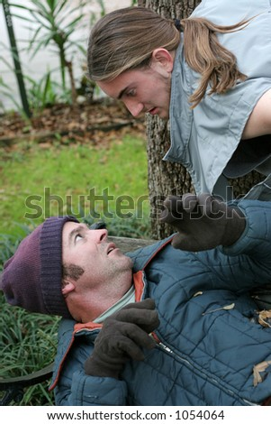 A homeless man afraid of a hostile young man. - stock photo