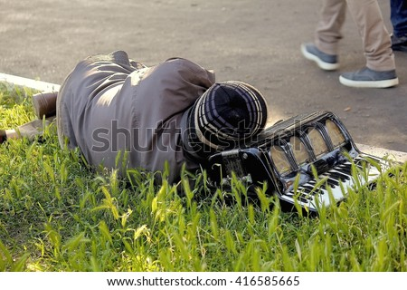 A Homeless man and his accordion sleeping in the park