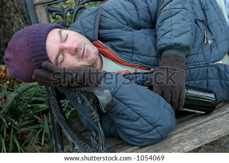 A homeless man asleep on a park bench with a bottle of wine in his hand. - stock photo