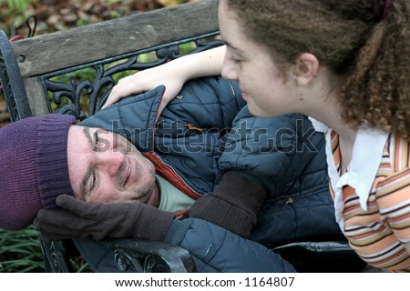 A homeless man being helped by a teen volunteer. (focus on homeless man's eyes) - stock photo