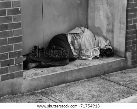 A Homeless Man bundled up under a jacket asleep in a city doorway - stock photo