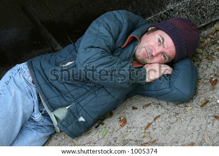 A homeless man lying on the ground. - stock photo