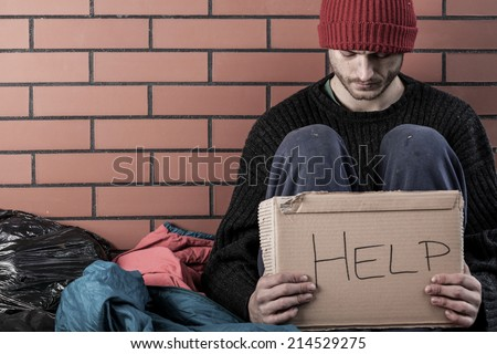 A homeless man need money and asks for help - stock photo