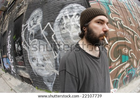 A homeless man on the city streets, filled with anxiety and hopelessness. Shot with fish-eye lens. - stock photo