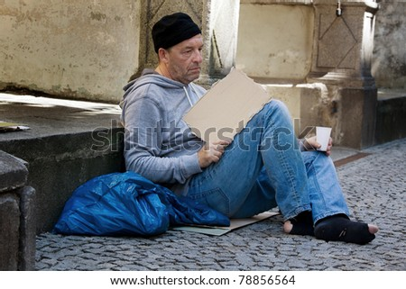 A homeless person looking for new work. Arbietsloser beggars living on the street. - stock photo