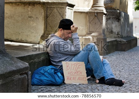A homeless person looking for new work. Unemployed beggars living on the street. - stock photo