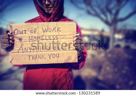 a homeless person with a sign - stock photo