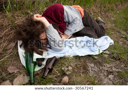 A homeless unemployed man laying in the ditch - stock photo