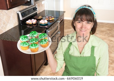 A homemaker displays a set of green cupcakes with clover sprinkles in her kitchen. - stock photo