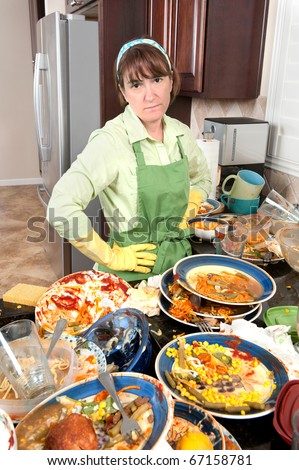 A homemaker get ready to wash dishes with little enthusiasm. - stock photo