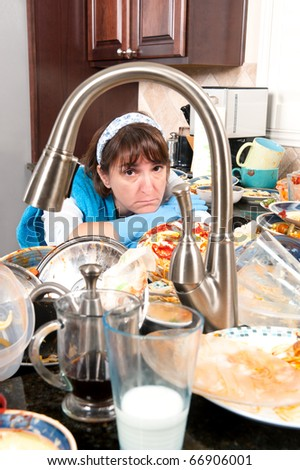 A homemaker gets ready to wash dishes with little enthusiasm. - stock photo