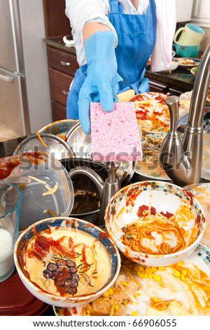 A homemaker offers her dish sponge to help wash dishes - stock photo