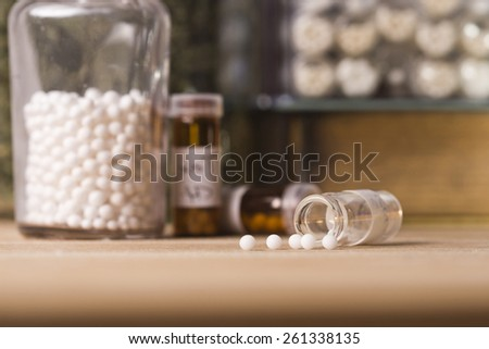 A homeopathy concept with homeopathic medicine (sugar/lactose pills and liquid homeopathic substances) - stock photo