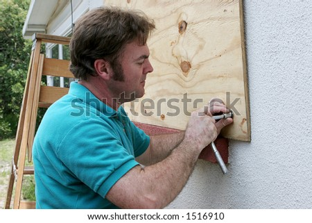 A homeowner or handy man screwing plywood onto windows in preparation for a hurricane. - stock photo