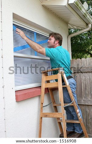 A homeowner or handyman is putting masking tape over windows to protect against broken glass during a hurricane. - stock photo