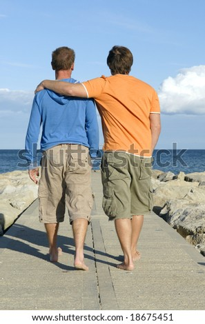 A homosexual couple take a leisurely walk along a beach pathway. - stock photo