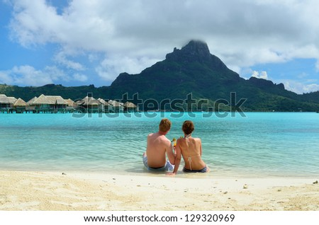 A honeymoon couple drinking a cocktail on the beach of a luxury vacation resort in the lagoon with a view on the tropical island of Bora Bora, near Tahiti, in French Polynesia. - stock photo