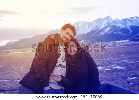 A honeymooner caucasian man and asian woman traveling and holding each other in winter with  snow  covered mountain background at Colorado USA, vintage filtered tone. - stock photo