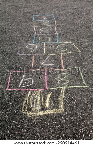 A hop scotch game is drawn on the road with chalk.
