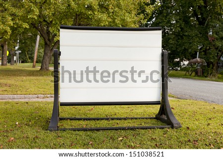 A horizontal blank white sign in a neighborhood with blurred background.