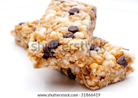a horizontal close up of two granola bars on a white plate - stock photo