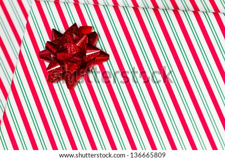 a horizontal close up shot of a gift with striped wrapping paper and a ribbon bow.  - stock photo