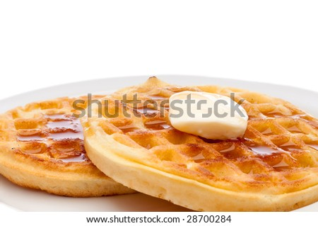 A horizontal closeup of two frozen breakfast waffles with a pat of butter and maple syrup on a white plate - stock photo