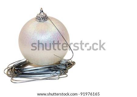 A horizontal color photograph of a Christmas ornament sitting on a pile of extra hooks.