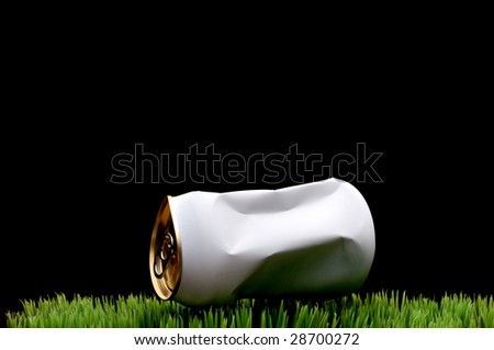 A horizontal image of a white crushed soda can tossed on green grass instead of being recycled - stock photo