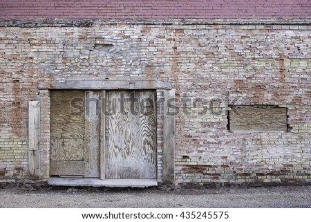 A horizontal image of an old brick building, with a boarded up door and window. This building was photographed in Winslow, Arizona.