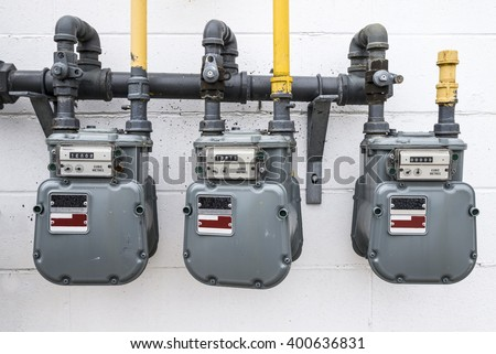 A horizontal image of natural gas meters hanging outside on a white wall of a building. - stock photo