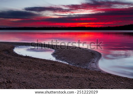 A horizontal image of sunrise on a sandy shoreline of Longview Lake.  Longview Lake is located just outside of the Kansas City, Missouri area. - stock photo