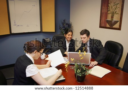 A horizontal shot a businessman and two businesswomen looking at papers and laptops. - stock photo
