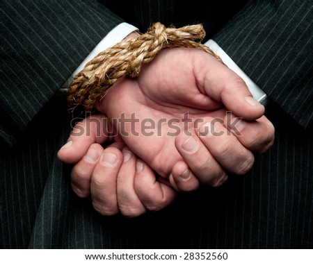 "A horizontal view of a business man with his hands tied behind him. Concept:""My hands are tied"" - stock photo"