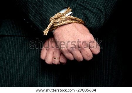 "A horizontal view of a business man with his hands tied infront of him. Concept:""My hands are tied"" - stock photo"