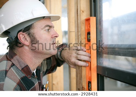 A horizontal view of a carpenter checking a newly installed window to see if it's level.  Authentic and accurate content. - stock photo