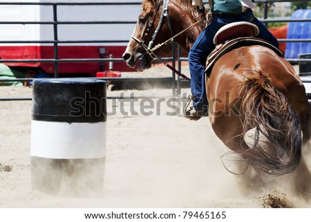 A horse and rider barrel racing at a rodeo. - stock photo