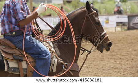 A horse eager to begin a roping competition carries a rider with a bright orange lariat. - stock photo