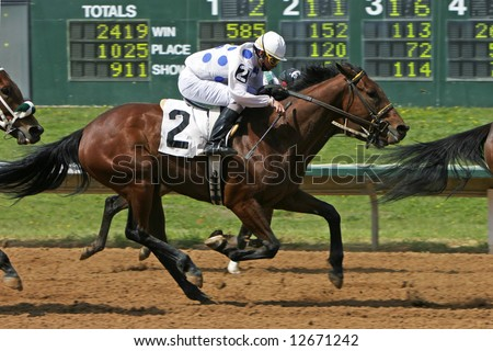 A horse race with a number of horses bunched together approaching the finish line, with the scoreboard in the background (focus point on the #2 horse). - stock photo