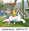A horse ride on the merry go round in a rural amusement park. - stock photo