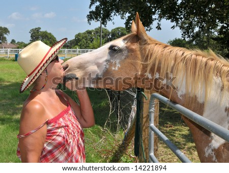 A horse shows affection to its female owner - stock photo