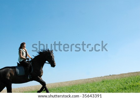 A horse with a rider climbs on the hillside. - stock photo