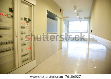 A hospital hallway with an electronics cabinet and bright window - stock photo