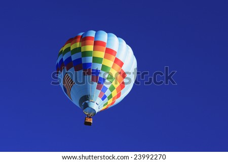 A hot air balloon ascending into the beautiful blue sky.